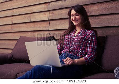 A mid shot of cute young lady wearing red check shirt, sitting on the couch with the laptop on the knees. Smiling girl spending time indoors