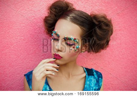 Closeup portrait of girl closed eyes and creative professional unusual fashionable makeup.Picture of pretty girl with hair in two bunches.Creative Make-up Background.Creative fashion beauty portrait