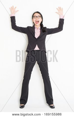 Full length front view of shocked young Asian businesswoman in formalwear bang and leaning on wall, standing on plain background.