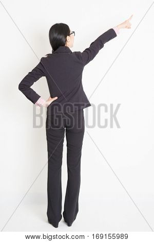 Full body back view of young Asian businesswoman in formalwear finger pointing on something, standing on plain background.
