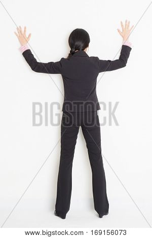Full body back view of young Asian businesswoman in formalwear banging on wall, standing on plain background.