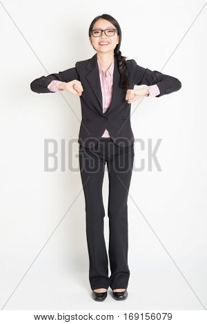 Full length front view of young Asian businesswoman in formalwear ready to jump, standing on plain background.
