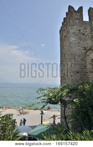 SIRMIONE, ITALY - AUGUST 7, 2014: People sunbathing next to the castle in the lake Garda Italy