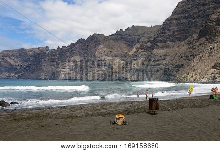LOS GIGANTES, SPAIN - OCTOBER 15, 2014: Tourists are visiting the Guios beach in Los Gigantes at foot of Gigantes cliffs on October 15, 2014 on Tenerife Island, Canary Islands, Spain.