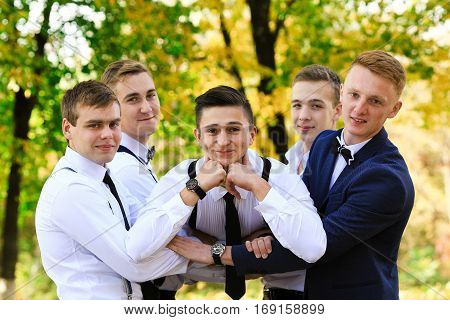 True men friendship. Group of handsome stylish men enjoying time together on wedding of their friend. Smiling happy cheerful men spend time together outdoors in spring, summer. Old friends.