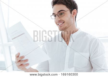 Picture of smiling man dressed in white shirt holding documents near big white window.