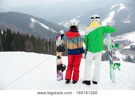 Back view picture of loving couple snowboarders on the slopes frosty winter day.