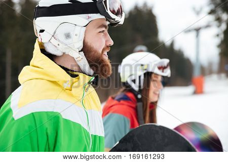 Picture of happy loving couple snowboarders on the slopes frosty winter day. Look aside.
