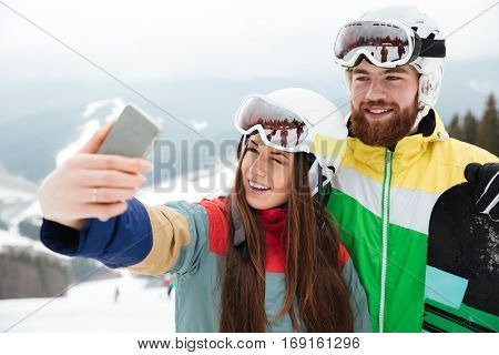 Image of cheerful loving couple snowboarders on the slopes frosty winter day making selfie by the phone.