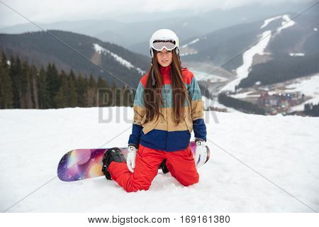 Photo of young lady snowboarder sitting on the slopes frosty winter day. Look at camera.