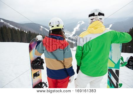 Back view photo of young loving couple snowboarders on the slopes frosty winter day.