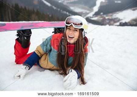Image of young laughing lady snowboarder lies on the slopes frosty winter day. Look at camera.