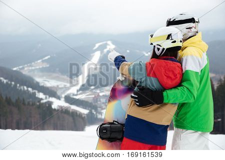 Back view picture of loving couple snowboarders on the slopes frosty winter day pointing.