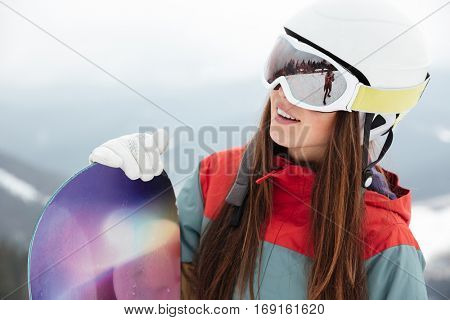 Photo of pretty woman snowboarder on the slopes frosty winter day. Look aside.
