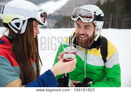 Image of happy loving couple snowboarders on the slopes frosty winter day drinking hot coffee or tea. Look at each other.
