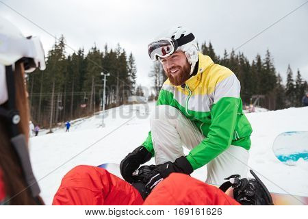 Picture of happy loving couple snowboarders on the slopes frosty winter day. Look at each other.