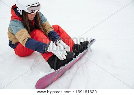 Picture of young lady snowboarder lies on the slopes frosty winter day. Look aside.