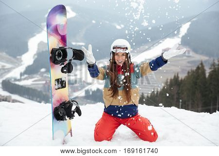 Image of cheerful lady snowboarder on the slopes frosty winter day. Look at camera.