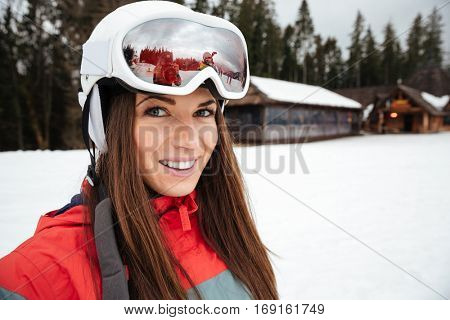 Photo of beautiful young woman snowboarder on the slopes frosty winter day. Looking at camera.