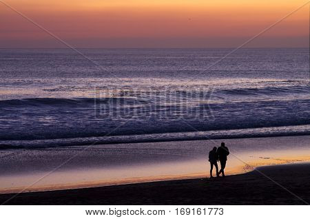 Couple Walking At Beach By Dusk
