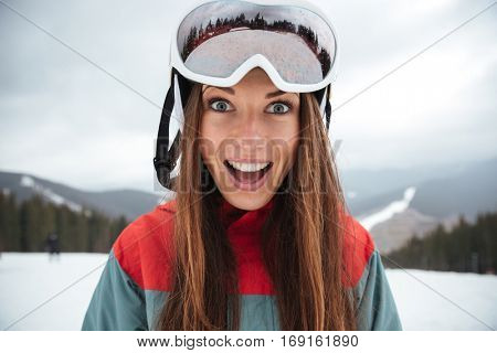 Photo of young excited happy lady snowboarder on the slopes frosty winter day. Look at camera.