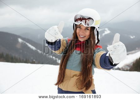 Picture of young beautiful lady snowboarder on the slopes frosty winter day making thumbs up gesture. Look at camera.