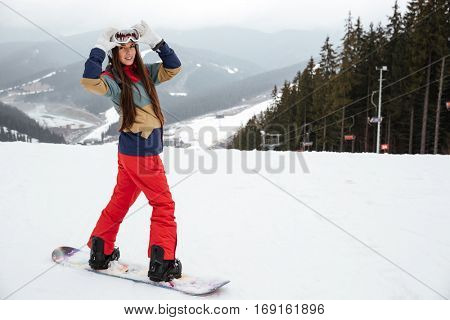 Picture of pretty young woman snowboarder on the slopes frosty winter day. Looking at camera.