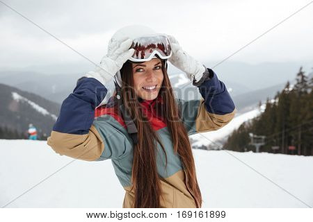 Photo of pretty young lady snowboarder on the slopes frosty winter day. Looking at camera.