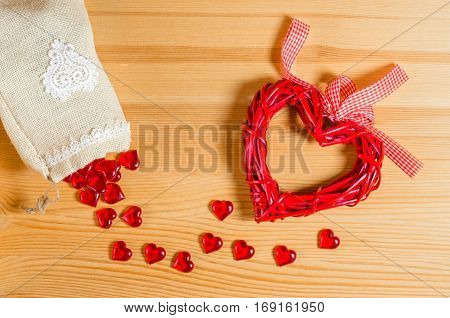Heart on a wooden texture, and spilling out of the bag with small glass hearts