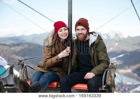 Image of young cheerful loving couple sitting in ropeway over mountains. Looking at camera.