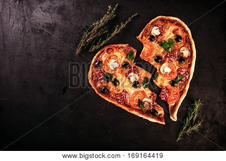 Heart shaped pizza with tomatoes and mozzarella for Valentines Day on vintage black background. Food concept of romantic heartbreak love