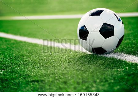 Traditional soccer ball on soccer field photographed in sunny day