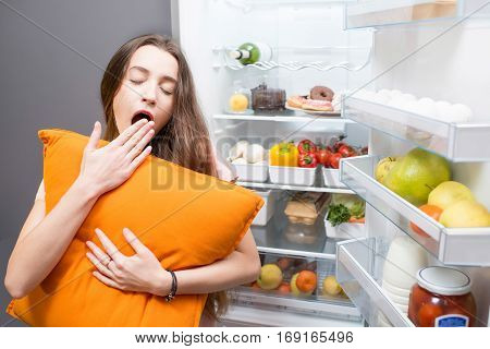 Young woman with pillow yawning standing in front of the refrigerator. Concept of eating during the night