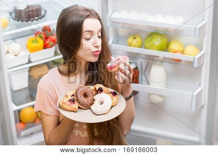 Portrait of a young sad woman in the sleepwear with sweet donuts standing near the open refrigerator