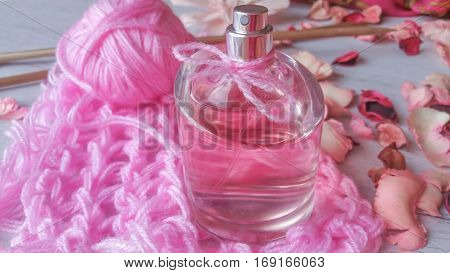 Perfume bottle with a delicate pink fragrance, yarn ball and rose petals