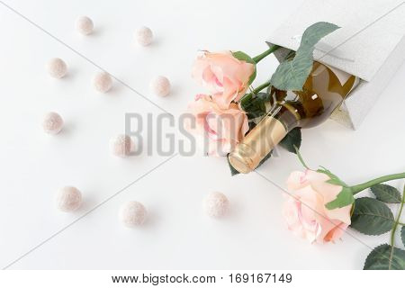 White wine bottle and three pink roses in a silver glitter gift bag on white background surrounded by champagne truffles.