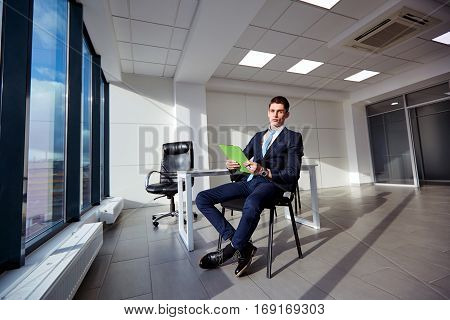 Businessman with documents in the hands of  modern office.