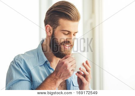Handsome bearded man in unbuttoned shirt is holding a cup and smiling while standing near the window at home