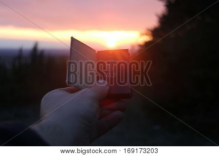 lets go wild text, Journey idea. Hand holding a book at sunset
