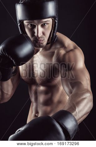 Boxing concept. Boxer with an aggressive look with boxing gloves before a fight on a black background