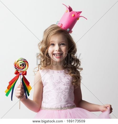 Beautiful little candy princess girl in crown holding big lollipop and smiling