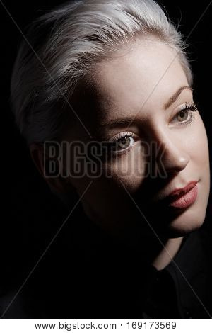Artistic photo of young blonde woman with short hair.