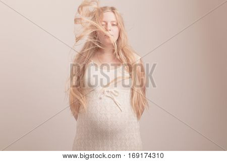 Pregnant woman caressing, touching her belly with hands over tummy