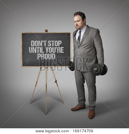 Don t stop until youre proud text on blackboard with businesssman holding weights