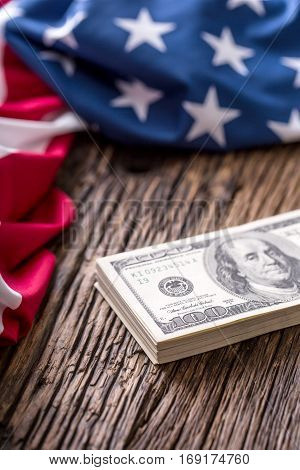 American dollars an Usa Flag.Close up of american flag and dollar cash money on old oak wood.