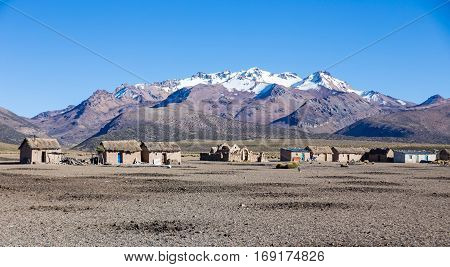 Small village of shepherds of llamas in the Andean mountains. High Andean tundra landscape in the mountains of the Andes. The weather Andean Highlands Puna grassland ecoregion of the montane grasslands and shrublands biome