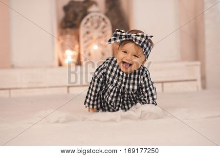 Laughing baby girl 1 year old crawling on floor wearing stylish headband and dress in room. Happy child. Childhood.