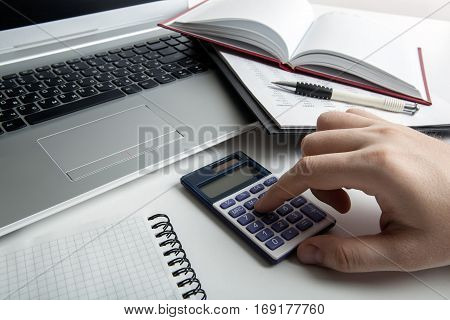 man working for a calculator and a computer in the office