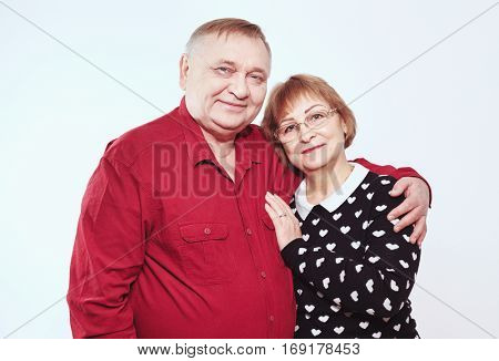 Portrait of aged couple hugging against white wall - happy retirement concept