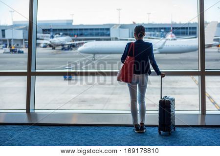 Businesswoman traveling in airport. Woman looking through the window at tarmac and planes waiting for flight. Business travel concept.